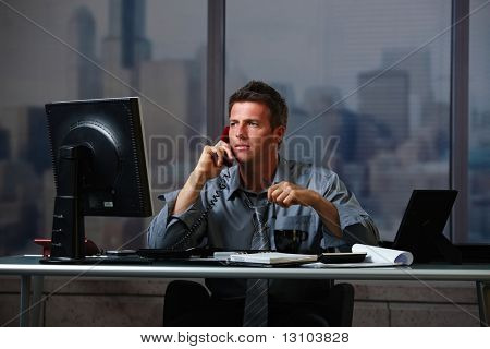 Tired businessman on call  working late holding glasses looking at screen doing overtime in office at night.