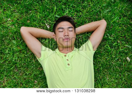 Portrait of asian student lying on a grass at a campus