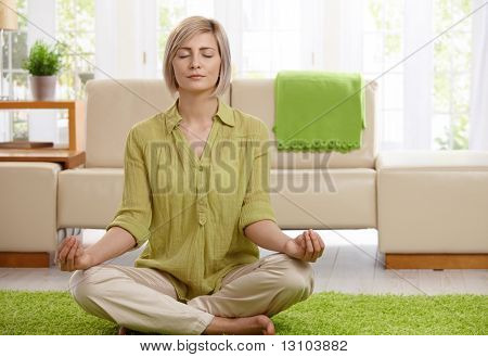 Woman sitting on floor at home doing yoga meditation.