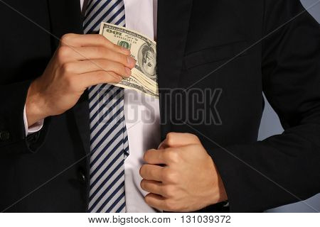 Man hiding dollar banknotes in suit