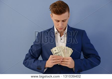 Attractive man in a suit holding fan of dollar banknotes on blue background