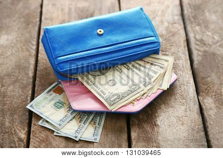 Open blue purse with dollar banknotes on wooden table
