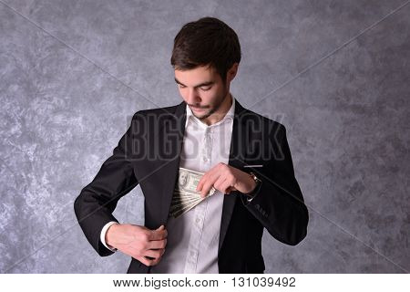 Attractive man hiding dollar banknotes in suit on grey background