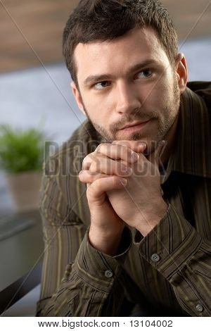 Serious young man looking determined sitting with hands folded.