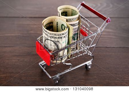 Small shopping trolley with dollars banknotes on wooden background