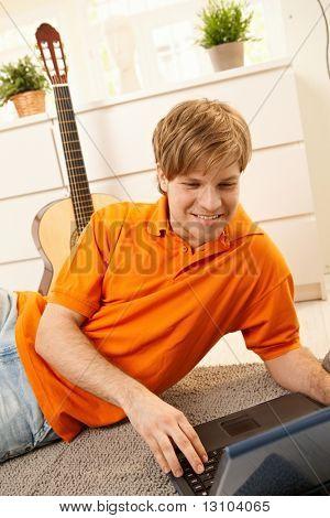 Porträt des jungen Mannes mit Laptop-Computer am Boden des Wohnzimmers, lächelnd.