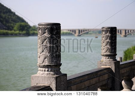 Decorative stone posts on a wall within Longmen Grottoes scenic area with a blurred background of the Yi River and longmen bridge.