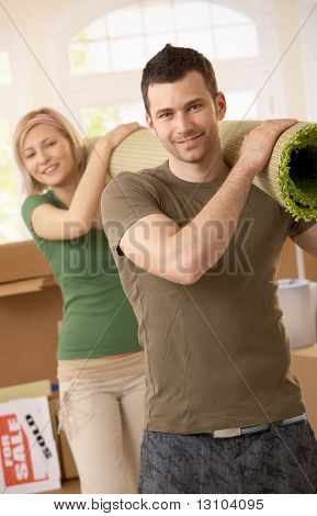Portrait of smiling couple moving place, carrying carpet on shoulder together.