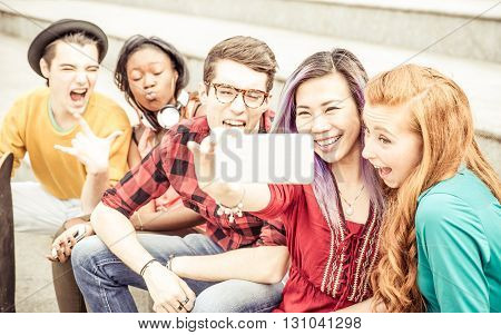 Group of teenagers sitting on the stairs and taking selfie