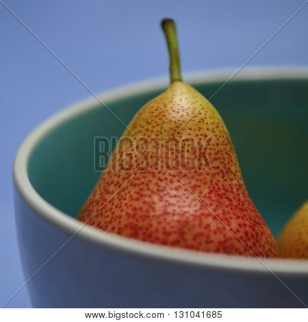 Extreme close up of a pear with bright red freckles in a blue bowl. Food photography.