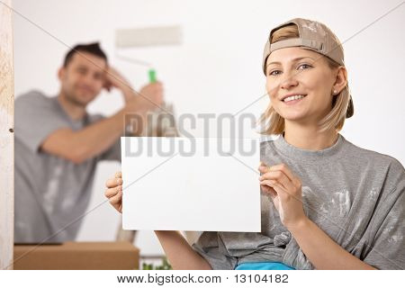 Smiling couple painting new house, woman in focus holding blank page, copyspace.