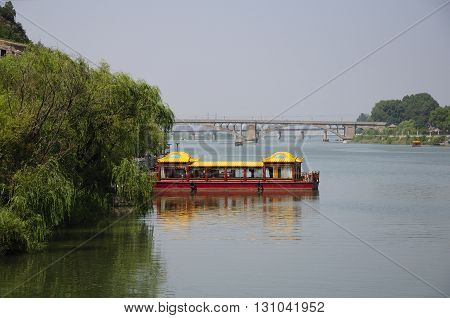 Chinese style tourist boats on the Yi River docked at Longmen Grottoes in Luoyang China in Henan province.