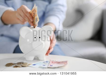 Female hand putting money into piggy bank closeup