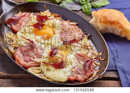 Pan of fried eggs with onion, ham, chard and basil on wooden table.