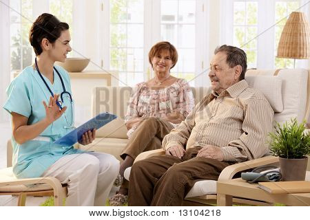 Nurse talking with elderly people and making notes during examination at home, smiling.