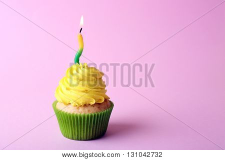 Birthday cupcake with candle on light pink background