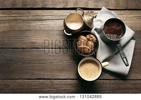 Mug of coffee with cookies on wooden table