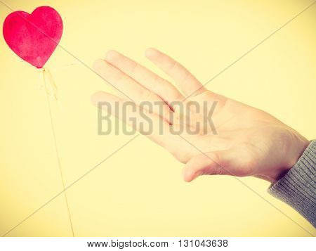 Male Hand With Little Heart On Stick.