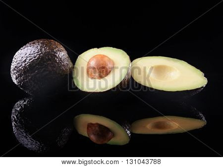 Fresh avocados on black background