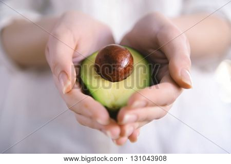 Female hands holding fresh avocado, closeup