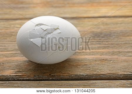 Cracked egg on wooden background