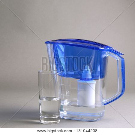 Water filter jug and a glass on the grey background