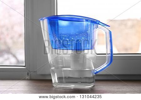 Water filter jug on the wooden windowsill
