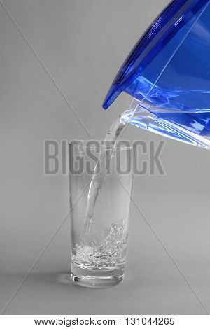 Filter jug pouring water in the glass, on the grey background, close-up