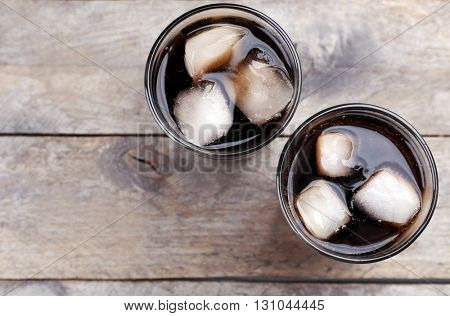 Glasses of soda water on wooden table, top view