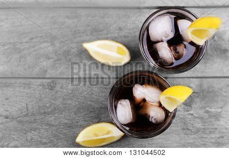 Glasses of soda water and sliced lemon on wooden table, top view