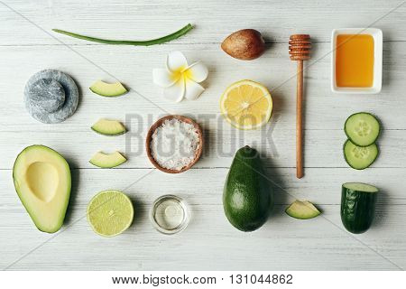 Still life with avocado oil on wooden table, top view