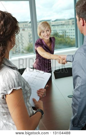 Successful job interview - happy employee shaking hands, smiling. Focus places on questionnarie in front, reults are excellent.