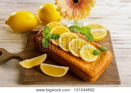 Delicious citrus cake loaf with lemons on wooden board
