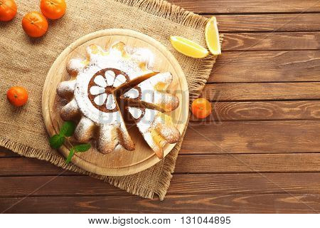 Delicious citrus cake with fruits on wooden board