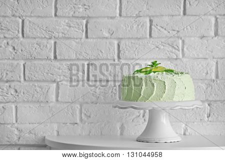 Big lime cake on a white stand beside brick wall