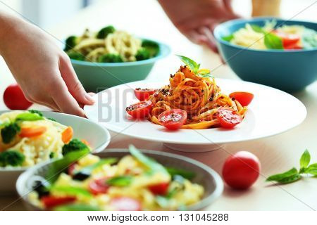 Different cold pasta salads in bowls on the table closeup