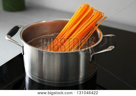 Boiling pasta in pan on electric stove in the kitchen