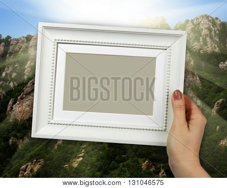 Wooden frame in beautiful woman hand mountains in the background