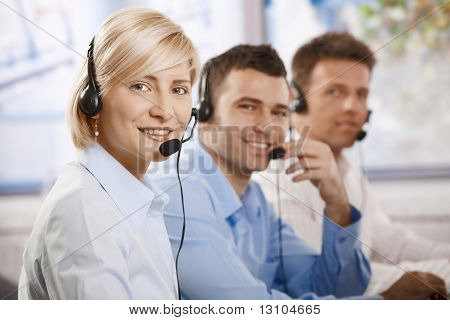 Happy young customer service operators talking on headset, looking at camera, smiling.