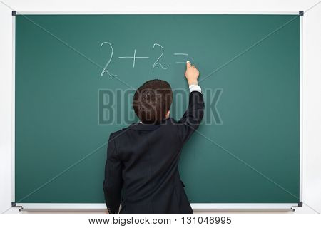 school boy decides examples math on chalkboard background, education exam concept