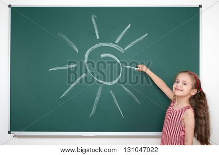 schoolgirl child in red striped dress drawing sun on green chalkboard background, summer school vacation concept