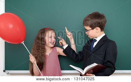school boy and girl child with balloon on chalkboard background having fun