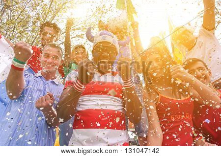 Multinational football supporters celebrating a goal in bar restaurant outdoors - Happy multiracial people having fun for - Sport against racism concept - Soft warm filter