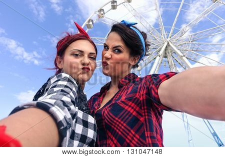 Pin up friends taking selfie in front of ferris wheel - Trendy girls making funny faces in phone camera - Retro 50's trends with new technology addiction concept - Soft warm saturated filter