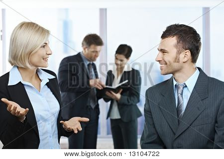 Standing businesspeople talking in office smiling at each other, coworkers looking at documents in background.