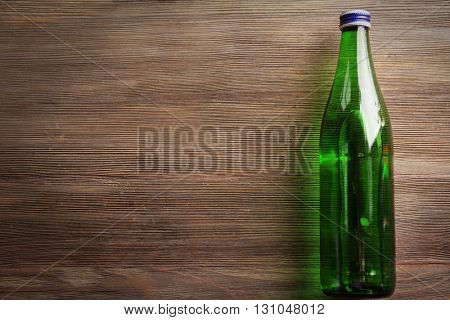 Bottle with soft drink on the wooden table, top view