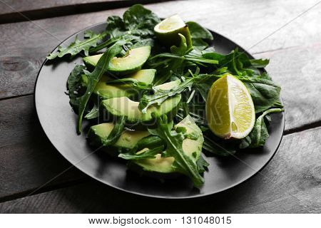 Sliced avocado with lime, spinach and arugula on black plate