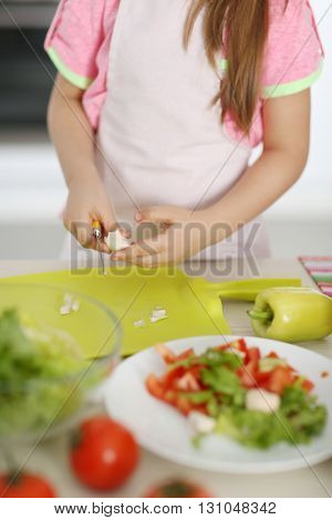 Little girl cutting vegetables for the salad in the kitchen