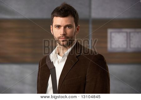 Portrait of stylish young man looking at camera in office lobby.