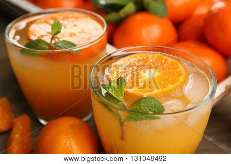 Delicious tangerine cocktails with ice, mint on a wooden table, close up